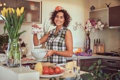 Het charmante krullende Spaanse meisje koken in haar keuken stock afbeeldingen