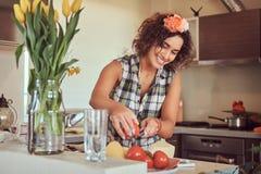Het charmante krullende Spaanse meisje koken in haar keuken royalty-vrije stock afbeelding