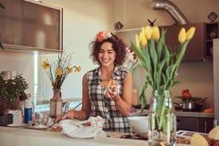 Het charmante krullende Spaanse meisje koken in haar keuken stock foto's