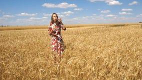 Het charmante meisje bevindt zich op een gebied op de hemelachtergrond en zet bellen in langzame motie stock videobeelden