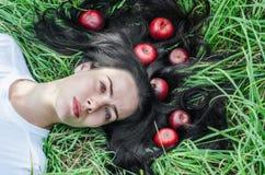 Het charmante meisje het brunette ligt op een groen gras op een open plek Haar ter plaatse Rode appelen in haar Het geheugen van  stock fotografie