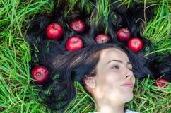 Het charmante meisje het brunette ligt op een groen gras op een open plek Haar ter plaatse Rode appelen in haar Het geheugen van  royalty-vrije stock fotografie