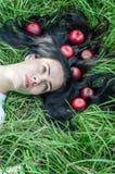 Het charmante meisje het brunette ligt op een groen gras op een open plek Haar ter plaatse Rode appelen in haar Het geheugen van  stock foto