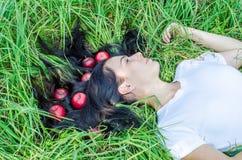 Het charmante meisje het brunette ligt op een groen gras op een open plek Haar ter plaatse Rode appelen in haar Het geheugen van  royalty-vrije stock foto