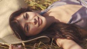 Het charmante meisje in een strohoed ligt in het gebied die en bij de camera letten op glimlachen Close-upportret van mooi stock footage