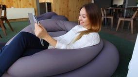 Het charmante meisje houdt tablet en zit op Internet die met glimlach op gezicht, als comfortabele voorzitter in koffie tijdens d stock video