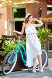 Het charmante meisje leunt tegen uitstekende fiets dichtbij de koffie van de de zomerstraat Royalty-vrije Stock Foto
