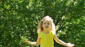 Het charmante Meisje met Blonde het Krullende Haar Stellen Bekijkend de Camera en Sluitend Haar Gezicht dient langs het Park in stock videobeelden