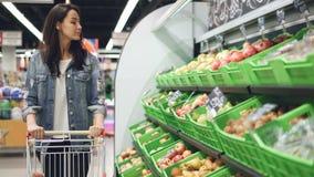 Het charmante meisje in toevallige kleding loopt langs fruitrij bewegend het winkelen karretje en het bekijken organisch fruit me stock videobeelden