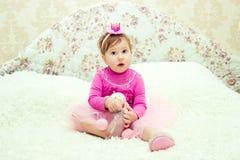 Het charmante meisje zit op het bed met een stuk speelgoed Stock Afbeeldingen