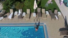 Het charmante vrouw ontspannen in de pool stock video