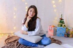 Het charmante vrouwelijke stellen op camera op Kerstavond en het zitten Stock Afbeeldingen