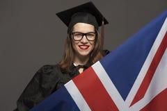 Het charmante vrouwelijke student glimlachen in oogglazen die zwarte mantel dragen stock foto