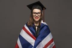 Het charmante vrouwelijke student glimlachen in oogglazen die zwarte mantel dragen royalty-vrije stock foto