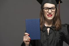 Het charmante vrouwelijke student glimlachen in oogglazen die zwarte mantel dragen royalty-vrije stock afbeelding