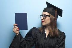 Het charmante vrouwelijke student glimlachen in oogglazen die zwarte mantel dragen royalty-vrije stock foto's