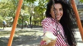 Het charmeren brunette die en roomijs op de speelplaats slingeren eten stock footage