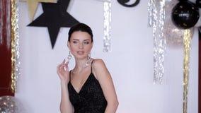 Het charmeren, stellend meisjesmodel in een zwarte kleding stock video