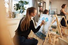 Het charmeren van blond meisje in glazen gekleed in zwarte blouse en jeans zit bij de schildersezel en schildert een beeld in het stock afbeeldingen