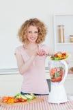 Het charmeren van blonde vrouw die een mixer in de keuken met behulp van Royalty-vrije Stock Foto's