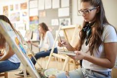 Het charmeren van bruin-haired meisje in glazen gekleed in witte t-shirt en jeans met een sjaal rond haar hals schildert een beel royalty-vrije stock foto