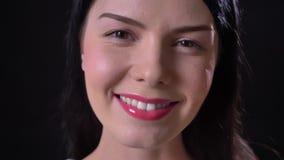 Het charmeren van donkerbruine jonge vrouw met roze camera bekijken en lippen die, zwarte achtergrond glimlachen stock footage