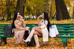 Het charmeren van donkerbruine meisjes die koffiezitting op bank in het park drinken Royalty-vrije Stock Foto's