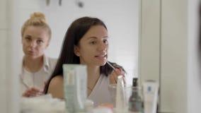 Het charmeren van donkerbruine vrouw die lippenstift op haar lippen voor een spiegel toepassen, de routine van de ochtendmake-up stock video