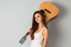 Het charmeren van donkerbruine vrouw met gitaar in handen Stock Fotografie