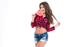 Het charmeren van gelukkige jonge vrouw die hart gevormde lolly eten stock foto