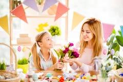 Het charmeren van glimlachende dochter die boeket van kleurrijke tulpen voorstellen royalty-vrije stock foto