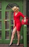 Het charmeren van jong blonde in het rode sexy kleding stellen voor een groen geschilderd deurkader Sensuele schitterende jonge v Royalty-vrije Stock Foto's