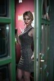 Het charmeren van jong blonde met het zilveren korte strakke geschikte kleding stellen in een groen geschilderd deurkader Sensuel Stock Foto