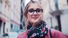 Het charmeren van jong meisje in een modieuze roze laag en zwarte glazen die aan muziek luisteren, en charmingly naar kijken stock video