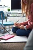 Het charmeren van jonge dame die in roze hoodie op notitieboekje schrijven stock fotografie