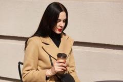Het charmeren van jonge donkerbruine vrouw met lang donker haar die laag dragen, zittend bij lijst in straatkoffie en het drinken royalty-vrije stock foto's