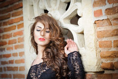 Het charmeren van jonge donkerbruine vrouw in zwarte kantblouse dichtbij een rode bakstenen muur. Sexy schitterende jonge vrouw me Royalty-vrije Stock Afbeelding
