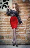 Het charmeren van jonge donkerbruine vrouw in zwarte kantblouse, rode rok en hoge hielen dichtbij de bakstenen muur. Sexy schitter Stock Foto