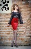 Het charmeren van jonge donkerbruine vrouw in zwarte kantblouse, rode rok en hoge hielen dichtbij de bakstenen muur. Sexy schitter Stock Fotografie