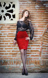 Het charmeren van jonge donkerbruine vrouw in zwarte kantblouse, rode rok en hoge hielen dichtbij de bakstenen muur. Sexy schitter Stock Afbeeldingen