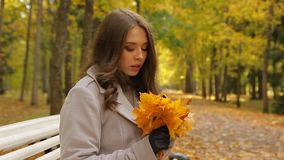 Het charmeren van jonge vrouw bekijkt dalende bladeren, en wacht op haar M. recht stock video