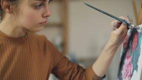 Het charmeren van jonge vrouwenschilder schildert bloemen bij de borstel van de canvasholding in vuile hand af en bekijkt beeld stock footage