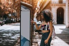 Het charmeren van krullend meisje betaalt in openlucht parkeermeter stock foto's
