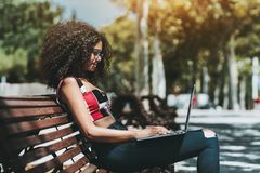 Het charmeren van krullend niet-gegradueerdenmeisje met laptop outoors royalty-vrije stock afbeelding