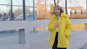 Het charmeren van modieuze blondevrouw in een modieus warm geel jasje die in stad in de herfst lopen stock video