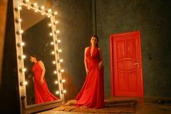 Het charmeren van mooi meisje in een avondavondjurk op een bontdeken dichtbij een reusachtige spiegel in een kader met bollen stock afbeeldingen