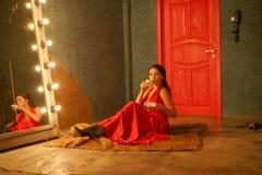 Het charmeren van mooi meisje in een rode lange avondjurk op een bontdeken dichtbij een reusachtige spiegel in een kader met boll royalty-vrije stock afbeelding