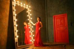 Het charmeren van mooi meisje in een rode lange luxeavondjurk op een bontdeken dichtbij een reusachtige spiegel in een kader met  royalty-vrije stock afbeeldingen