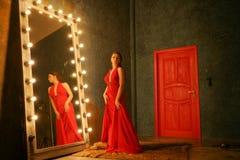 Het charmeren van mooi meisje in een rode lange luxeavondjurk op een bontdeken dichtbij een reusachtige spiegel in een kader met  stock fotografie