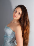 Het charmeren van mooie jonge vrouw in een blauwe kleding met lange dikke D Stock Fotografie